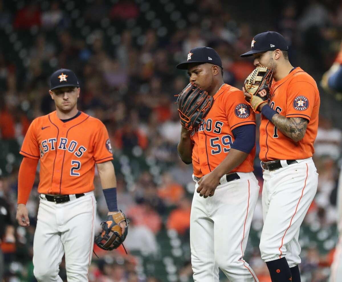 Houston Astros shortstop Carlos Correa (1) talks with starting pitcher Framber Valdez (59) after Oakland Athletics Starling Marte's single during the sixth inning of an MLB baseball game at Minute Maid Park, Friday, October 1, 2021, in Houston.