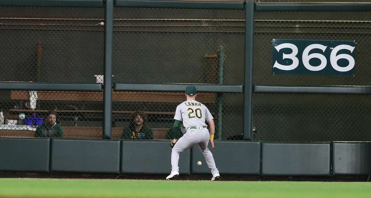 Oakland Athletics left fielder Mark Canha (20) chases Houston Astros Jake Meyers' RBI double during the sixth inning of an MLB baseball game at Minute Maid Park, Friday, October 1, 2021, in Houston.