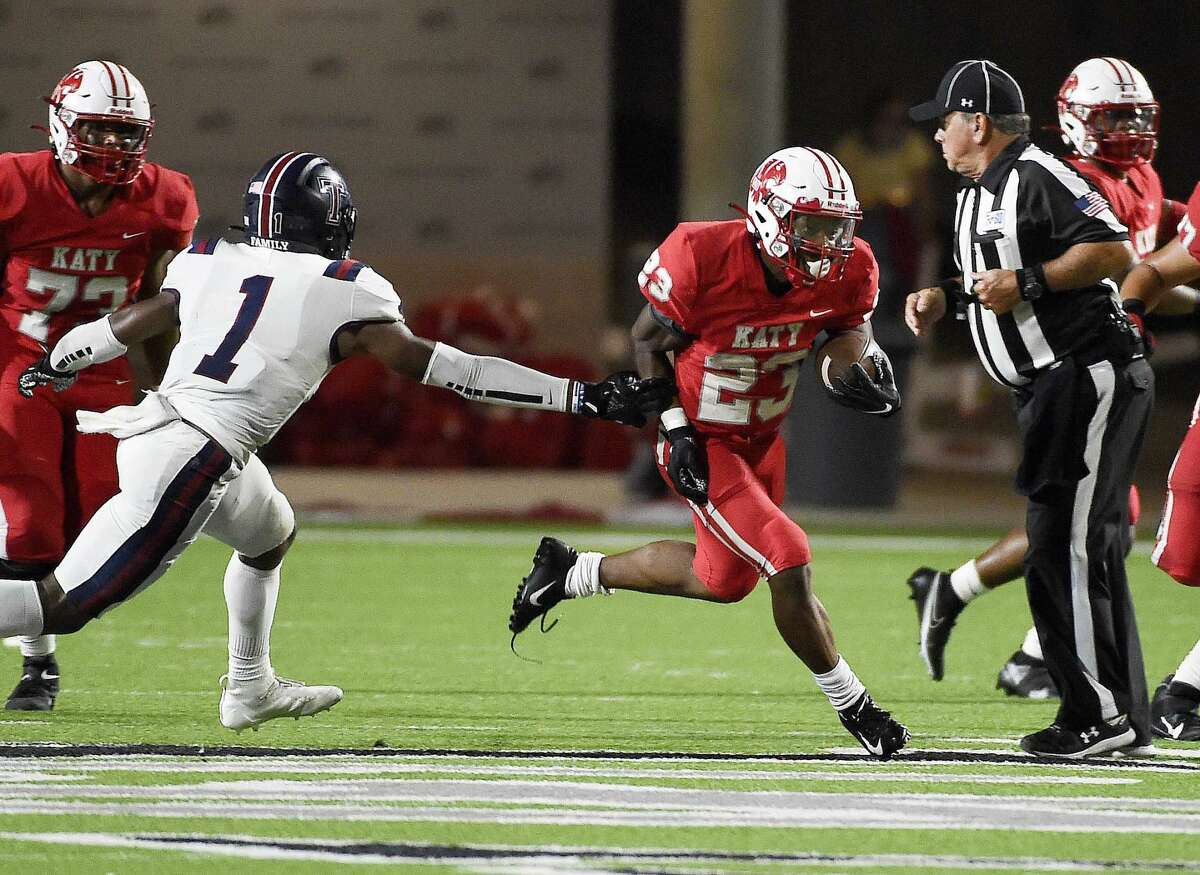 Katy running back Seth Davis (23) escapes the tackle of Tompkins defensive back Caleb Komolafe (1) and an official en route to a touchdown during the second half of a high school football game, Friday, Oct. 1, 2021, in Katy.