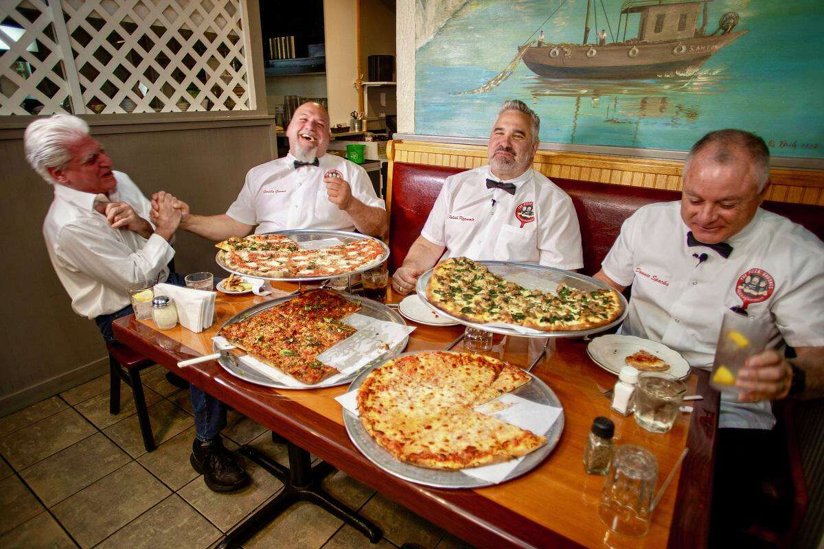 """From left to right: An unidentified patron of Abate Restaurant chats with the Pizza Gavones as they are about to review their pizza. The Gavones are from left to right: Timmy """"Gorilla Gavone"""" Byrd, Frank """"Polish Pizzaiolo"""" Zabski and Donald , """"Donnie Spocks"""" Cretella."""