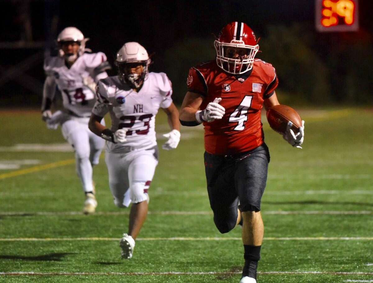 New Canaan's Vincent Cognetta runs away from North Haven's Sebastian DeRubeis (23) and MJ Devilliers during Friday's game at Dunning Stadium in New Canaan.