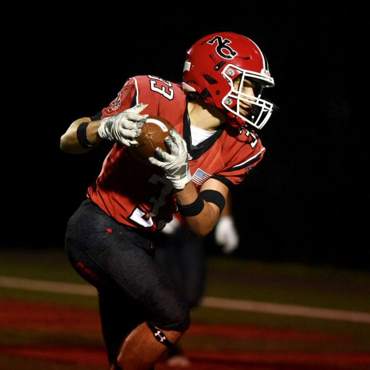 New Canaan's Hunter Telesco scores on a touchdown reception during a football game against North Haven on Friday at Dunning Stadium.