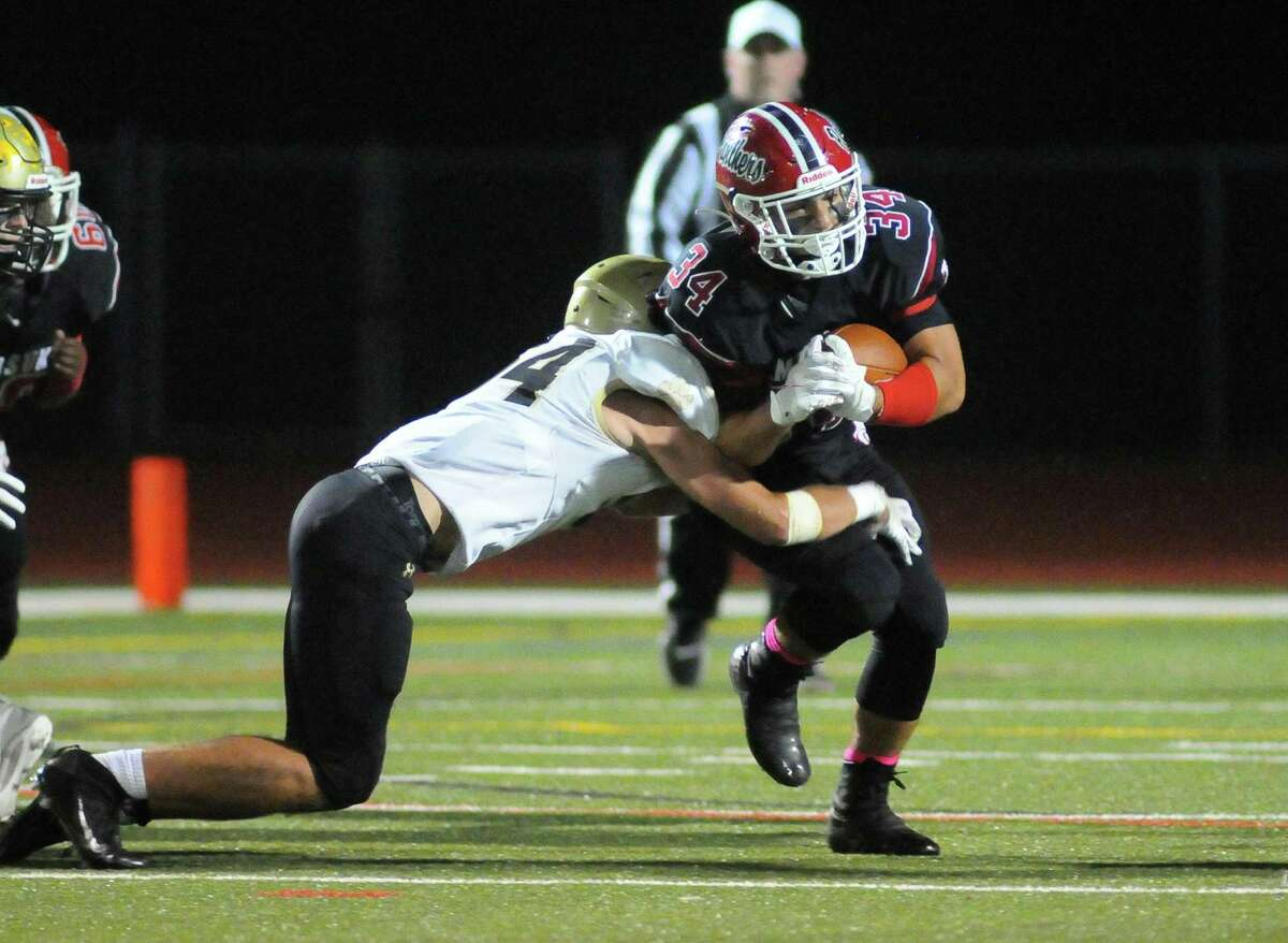 Masuk's Lukas Shamas (34) gets tackled by Daniel Hand's Brendan Walsh (54) during high school football action against Daniel Hand in Monroe, Conn., on Friday October 1, 2021.