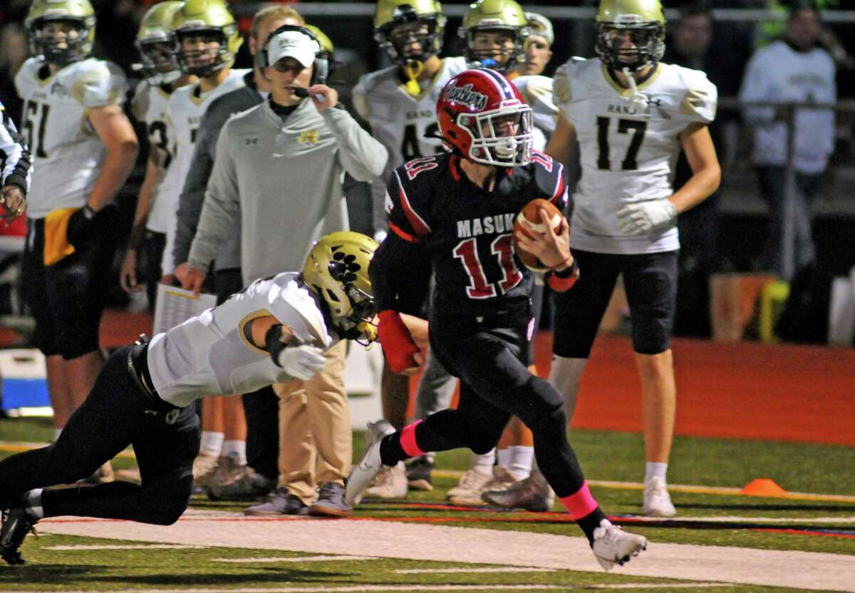 Masuk's Jake Dellapiano (11) carries the ball to the endzone to score a touchdown as Daniel Hand's Seth Sweitzer (5) tries to grab him during high school football action in Monroe, Conn., on Friday October 1, 2021.