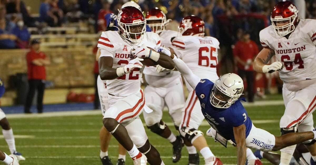 Houston running back Alton McCaskill (22) avoids a tackle by Tulsa safety Cristian Williams (3) and carries for a touchdown in the first half of an NCAA college football game Friday, Oct. 1, 2021, in Tulsa, Okla. (AP Photo/Sue Ogrocki)