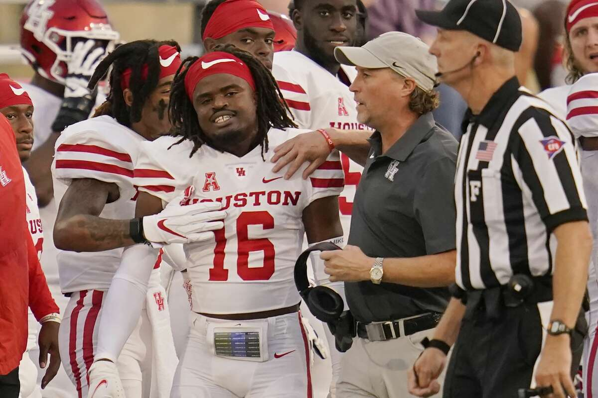 Houston head coach Dana Holgorsen, center, talks with cornerback Jayce Rogers (16) after Rogers was ejected from the game for targeting in the first half of an NCAA college football game against Tulsa, Friday, Oct. 1, 2021, in Tulsa, Okla. (AP Photo/Sue Ogrocki)