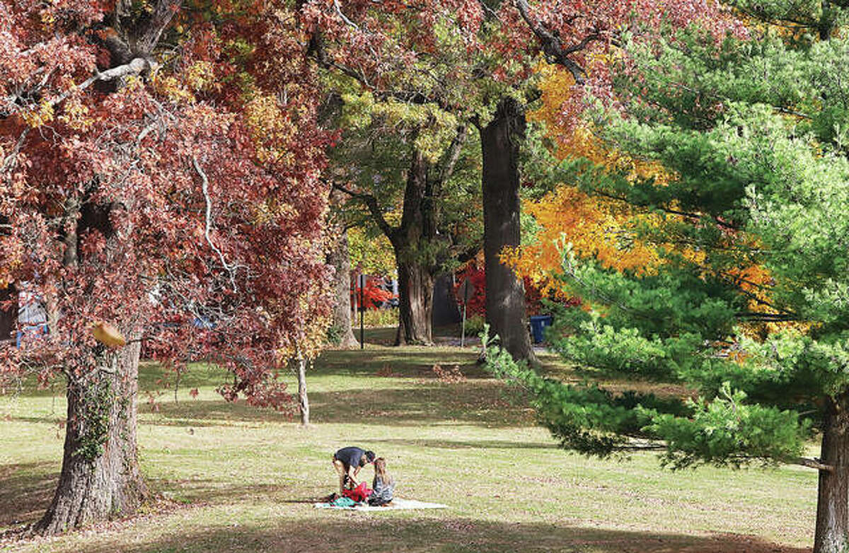 Two people set up a blanket at Alton's Haskell Park last year, taking advantage of sunshine for a picnic in the park surrounded by the fall colors. Guides to autumn drives are being offered by the Great Rivers and Routes tourism bureau and the Illinois Office of Tourism.