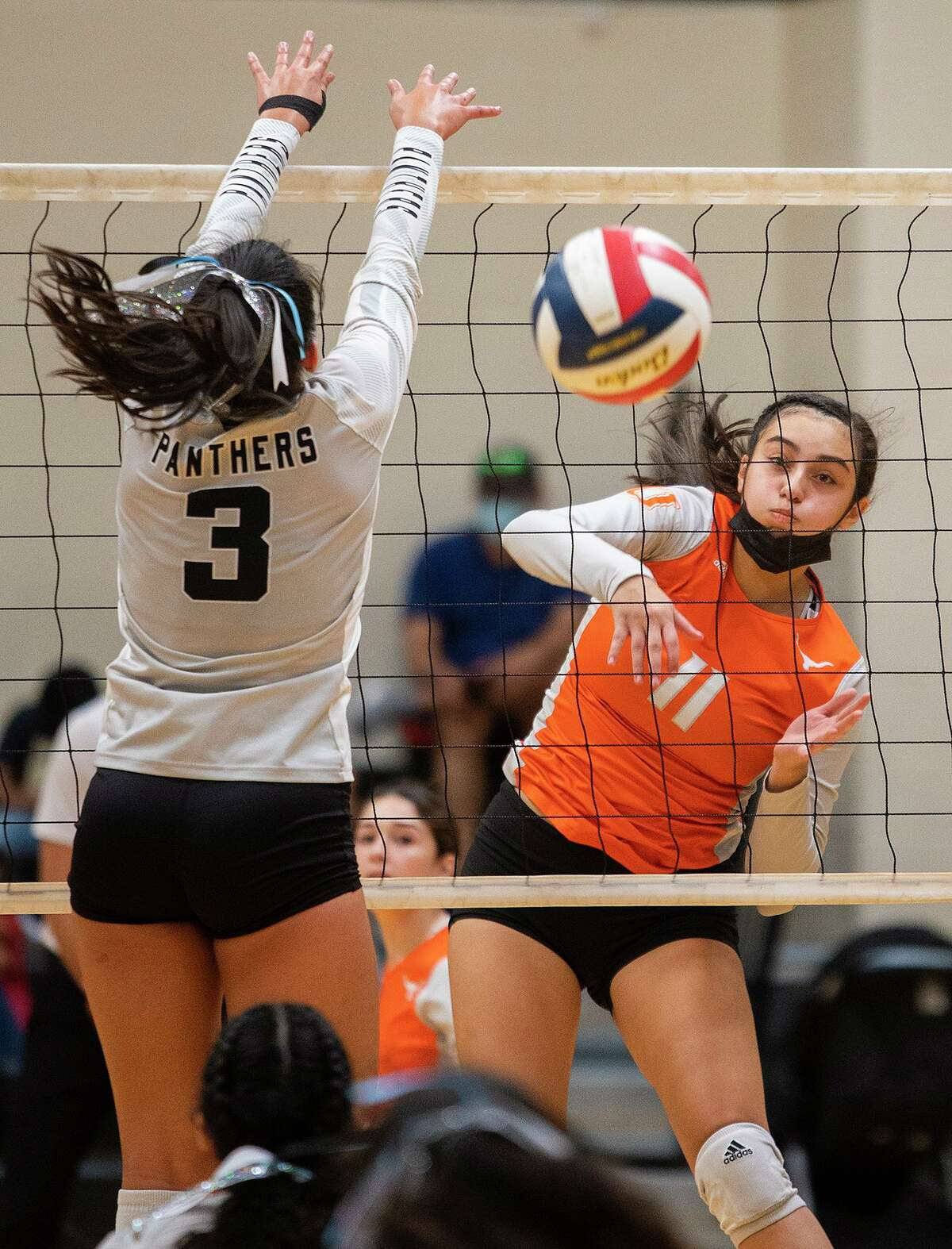 United High School Mia Molina goes for the kill as United South High School Sierra Sanchez goes for the block. Molina ranks No. 6 in the city with 226 kills on the season.