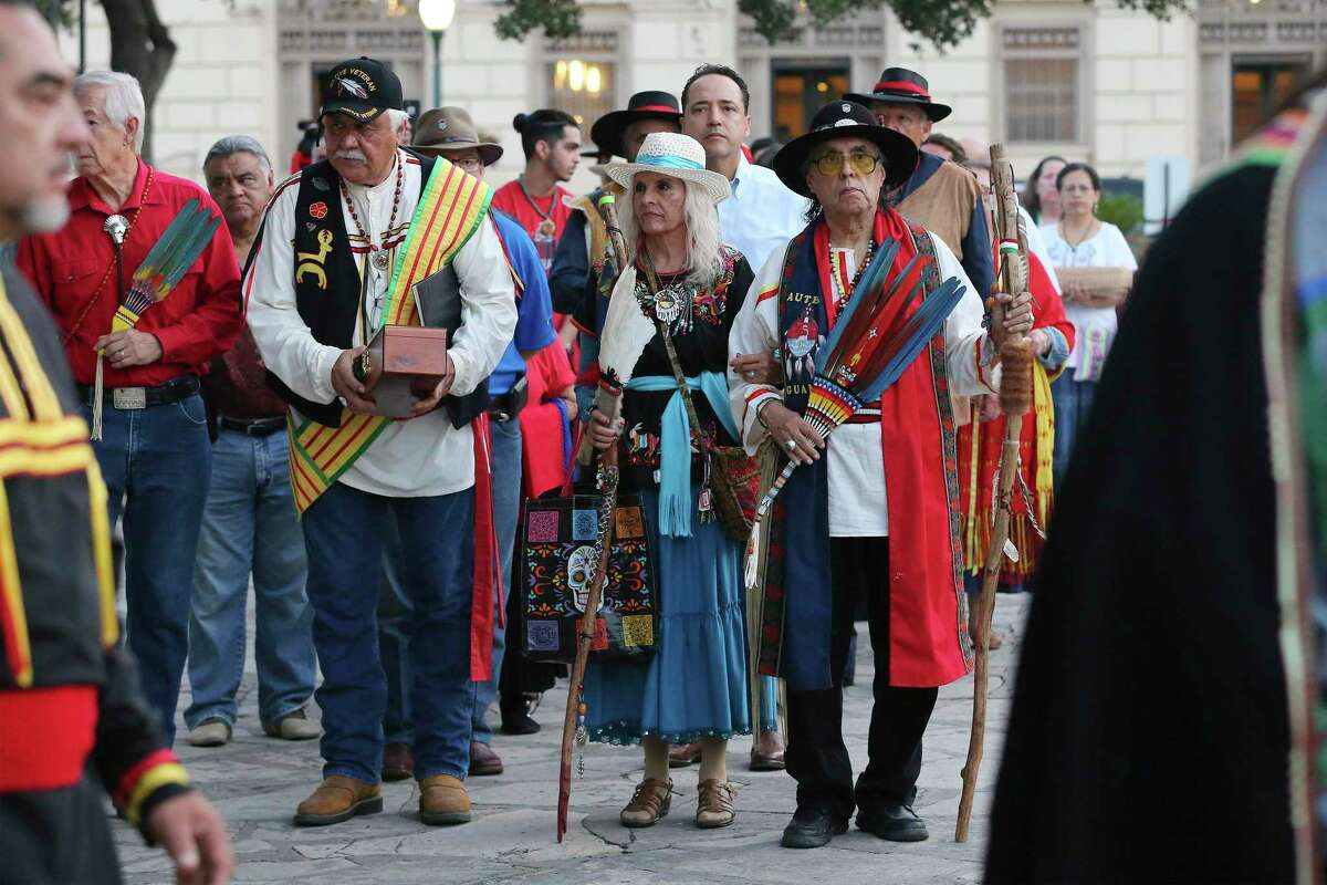 Ramón Vásquez y Sánchez (from right), his wife Maria Chavez Vásquez and Raymond Hernandez form a line as local Native Americans gather to honor buried descendants during their 25th Annual Sunrise Ceremony at the Alamo on Saturday, Sept. 7, 2019. In the background is the Hipolito F. Garcia Federal Building, where the first church of the Mission San Antonio de Valero may have been.