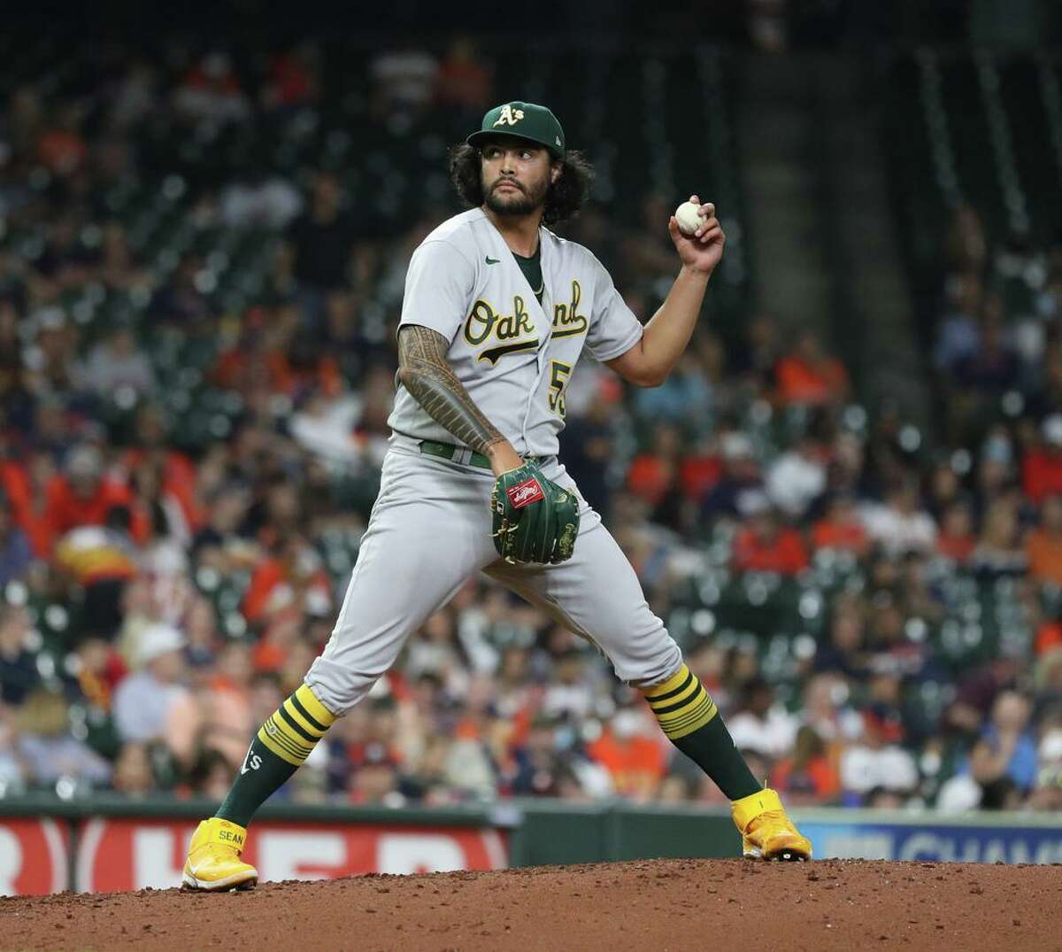 Oakland Athletics starting pitcher Sean Manaea (55) hesitates between pitches to Houston Astros Marwin Gonzalez during the third inning of an MLB baseball game at Minute Maid Park, Friday, October 1, 2021, in Houston.