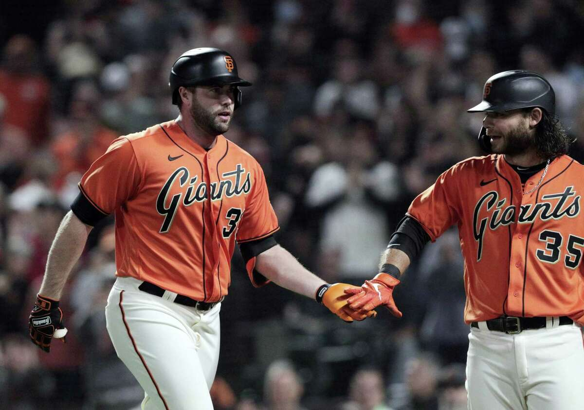 Brandon Crawford (35) high fives Darin Ruf (33) after he hit a solo homerun in the first as the San Francisco Giants played the San Diego Padres at Oracle Park in San Francisco, Calif., on Friday, October 1, 2021.,