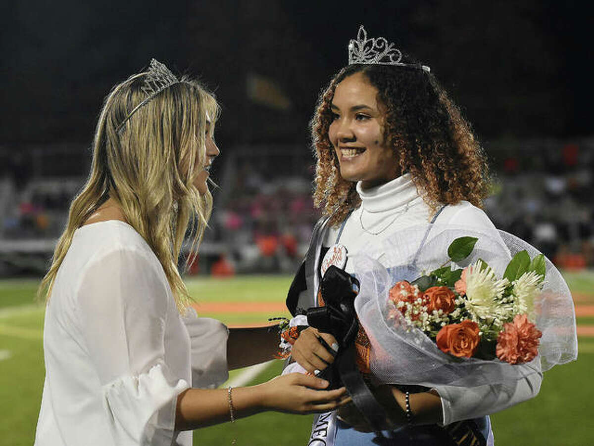 Edwardsville High School Homecoming Queen Sydney Harris, right, receives a bouquet of flowers from last year's Homecoming Queen, Anna Brase.