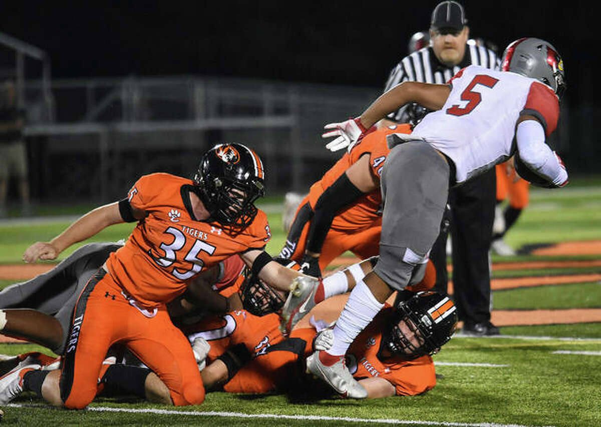 Edwardsville's Carson Forsting (No. 35) trips up Alton running back Keith Gilchrese in the first half on Friday in Edwardsville.