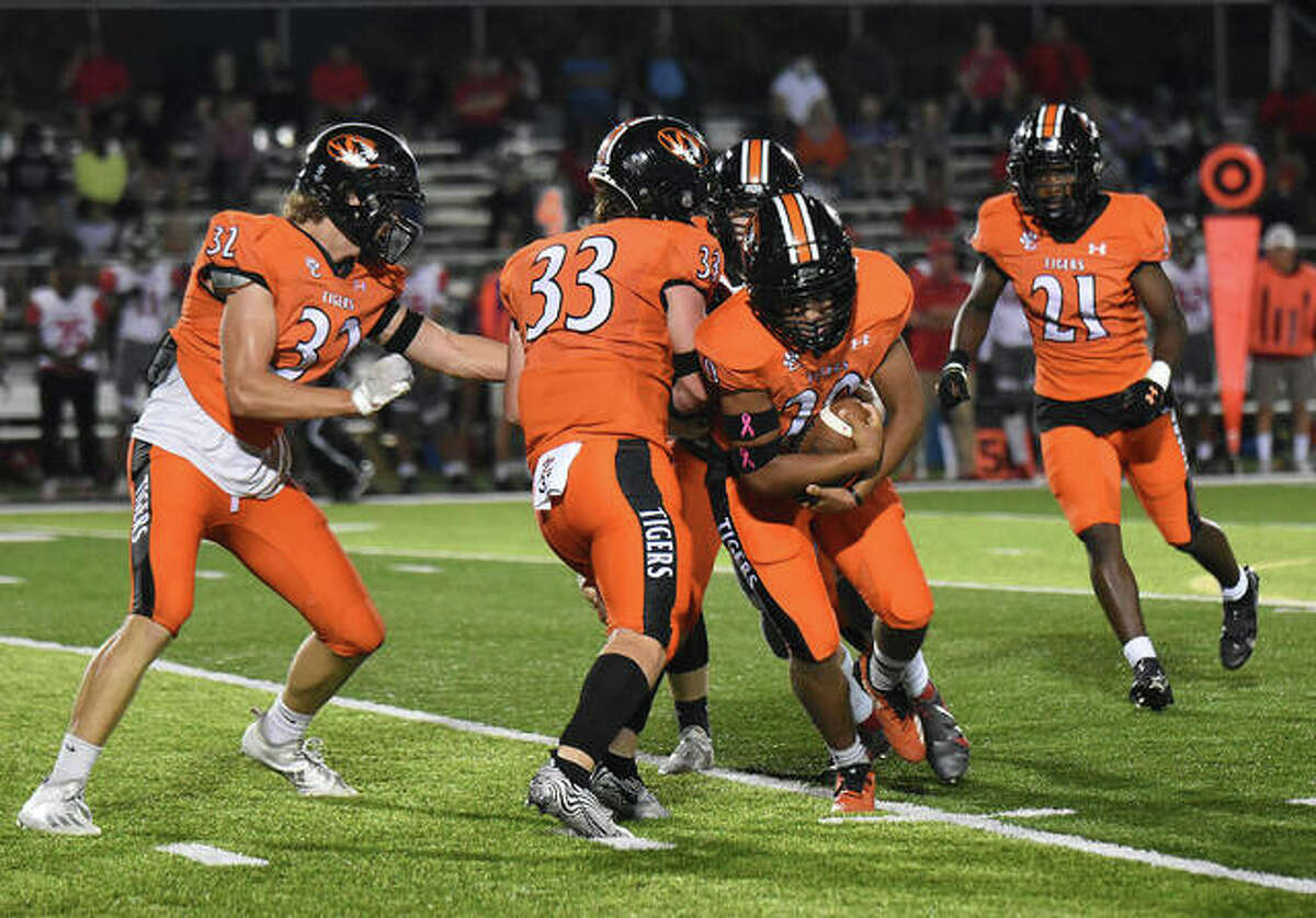 Edwardsville's Thomas Haire, third from right, recovers a blocked punt in the first half on Friday in Edwardsville.