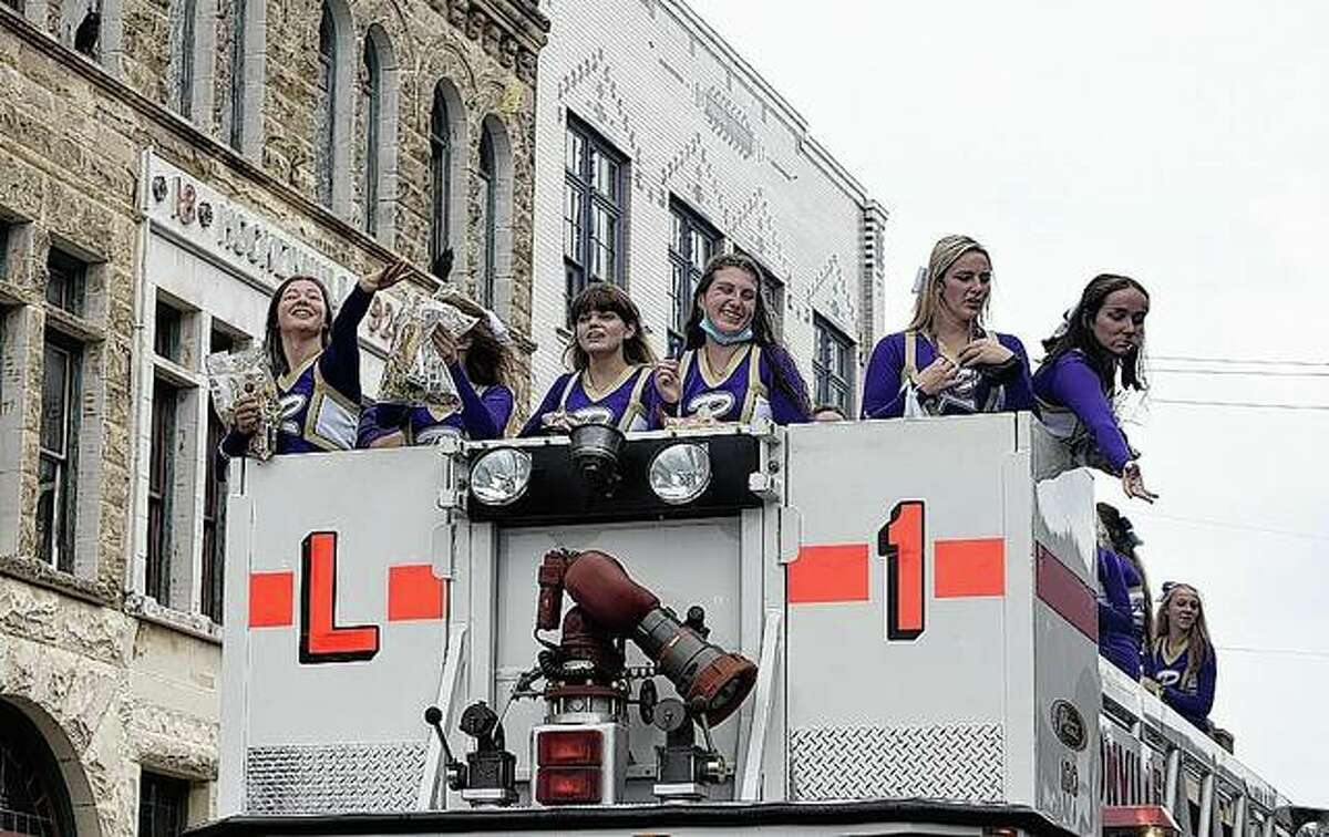 Routt Catholic High School cheerleaders toss candy Friday during the school's homecoming parade.