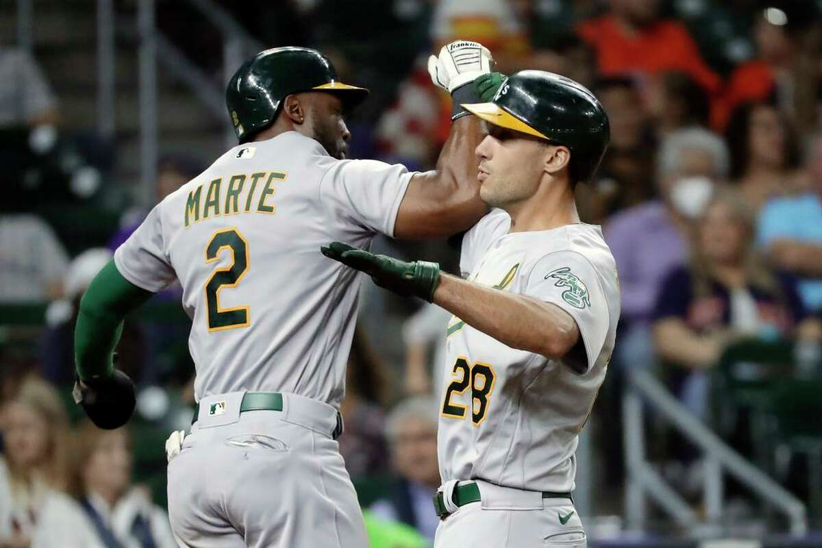 Oakland Athletics' Starling Marte (2) and Matt Olson (28) celebrate after they both scored on the two run home run by Olson during the sixth inning of a baseball game against the Houston Astros Friday, Oct. 1, 2021, in Houston. (AP Photo/Michael Wyke)