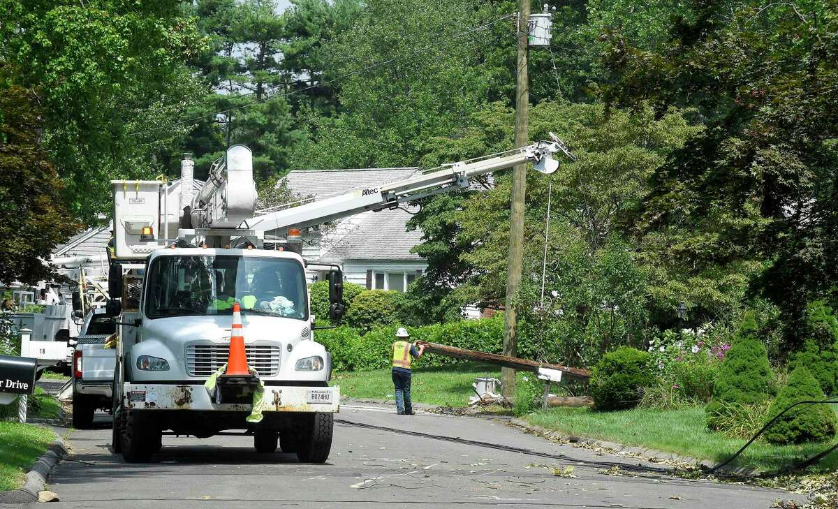 A utility crew from Service Electric Company based out of Chattanooga, Tennessee clears a broken utility pole from Bertmor Drive after restoring power to the neighborhood on August 11, 2020 in Stamford, Connecticut.