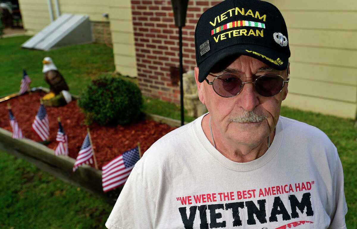 Vietnam veteran Clyde Jones and the memorial he erected in his garden Thursday, September 30, 2021, in Norwalk, Conn. Jones built the memorial for 13 US soldiers killed in the airport bombing during the US withdrawal from Afghanistan.