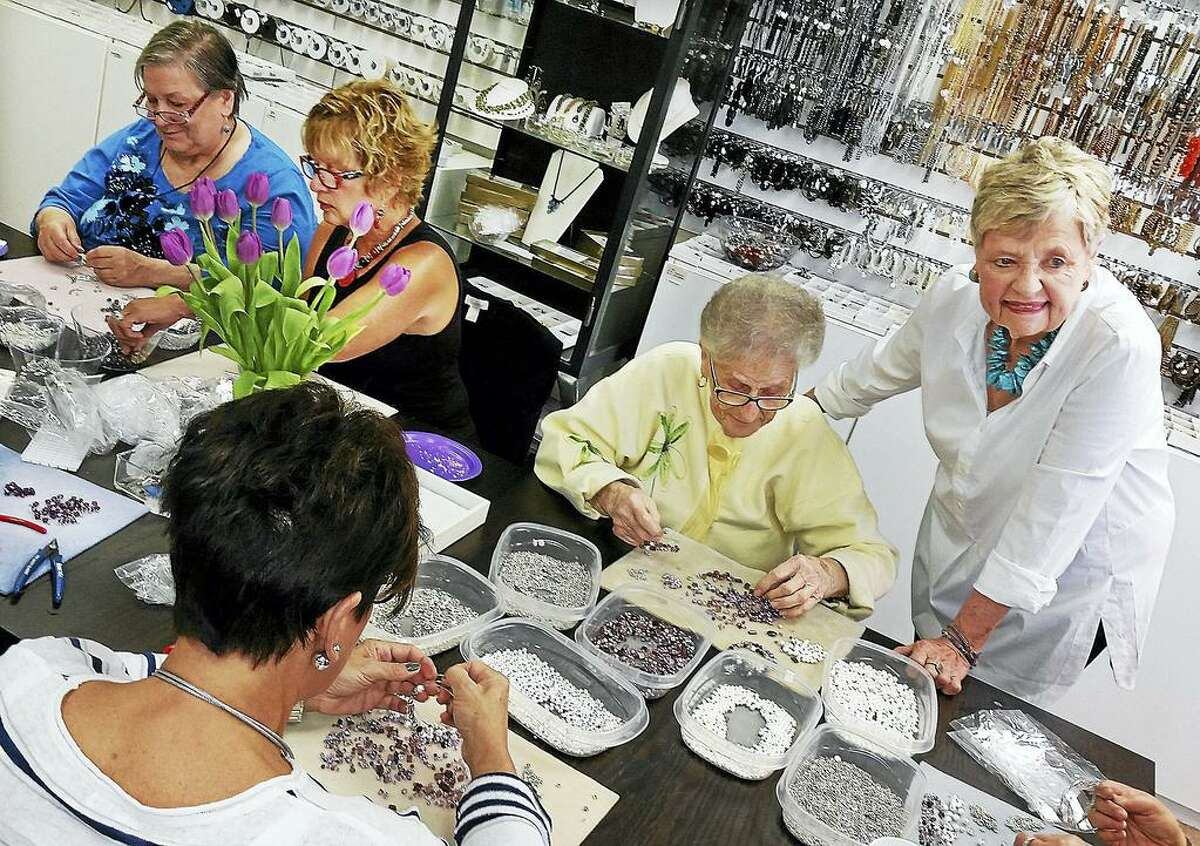 File photo: Rena Mulrain, at right, owner of the Bead Hive looks over volunteers Helen Wonoski,left, Kathy Spero, center, Wanda Bennett, right and Terri Maltese, back to camera, making Bracelets of Courage to help raise money for women who are physically abused in domestic violence.