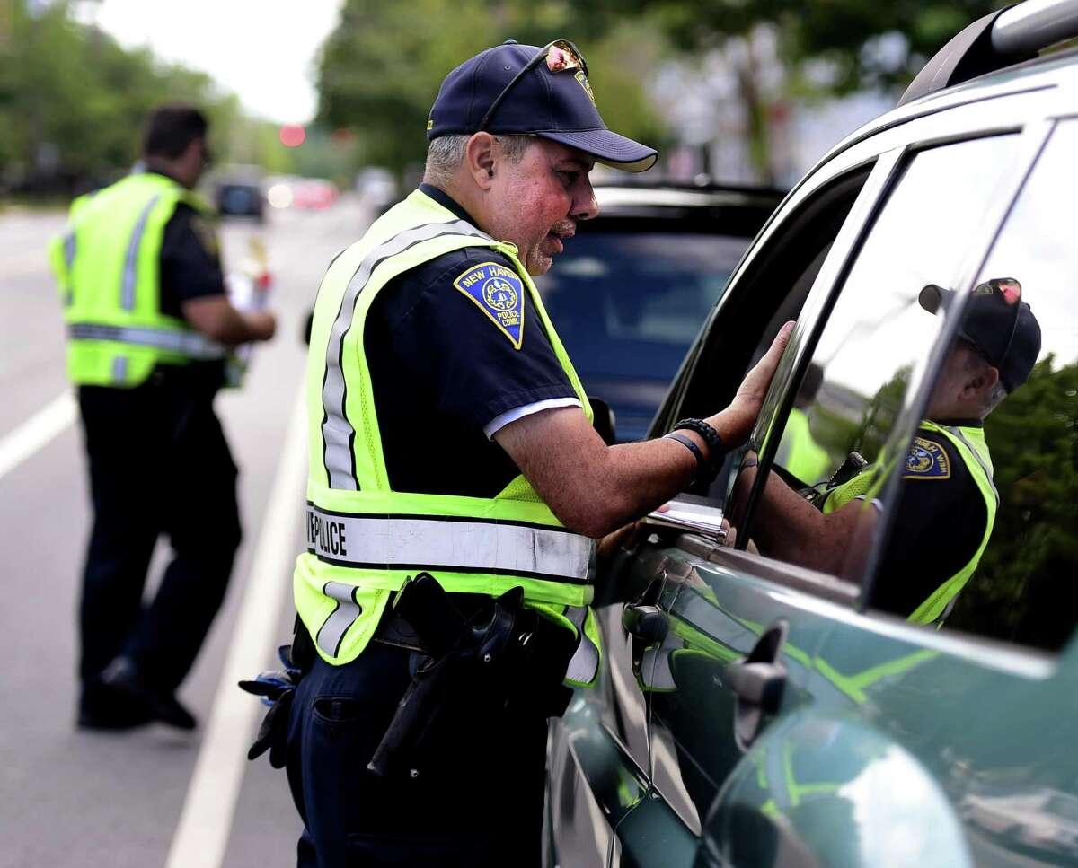 New Haven Police officer Salvadore Rodriguez talks to a driver pulled over for using a mobile phone Monday, August 8, 2016 on Dixwell Ave.