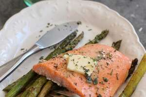 This photo shows baked steelhead trout with asparagus, potatoes and herbs in Concord, N.H. (AP Photo/Matthew Mead)