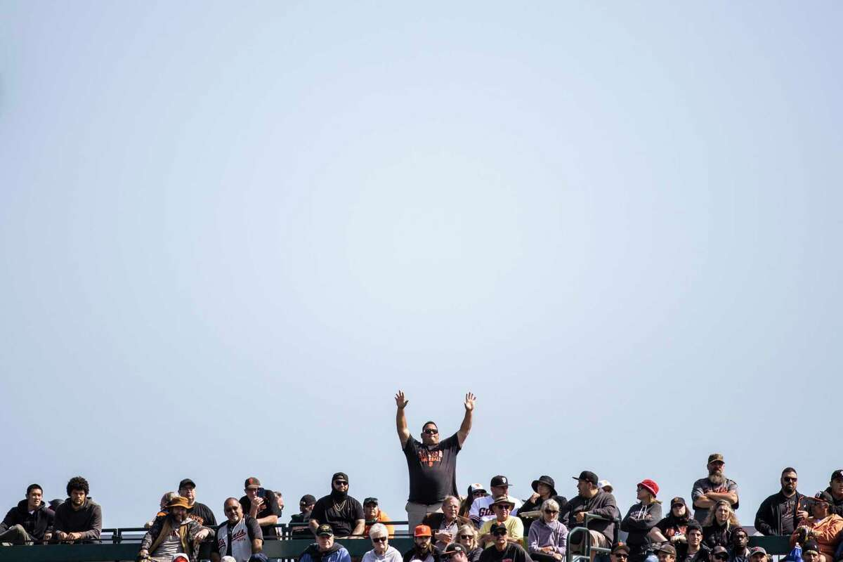 A baseball fan gestures on from the outfield during a MLB baseball game between the San Francisco Giants and the San Diego Padres at Oracle Park in San Francisco, California Thursday, Sept. 16, 2021.