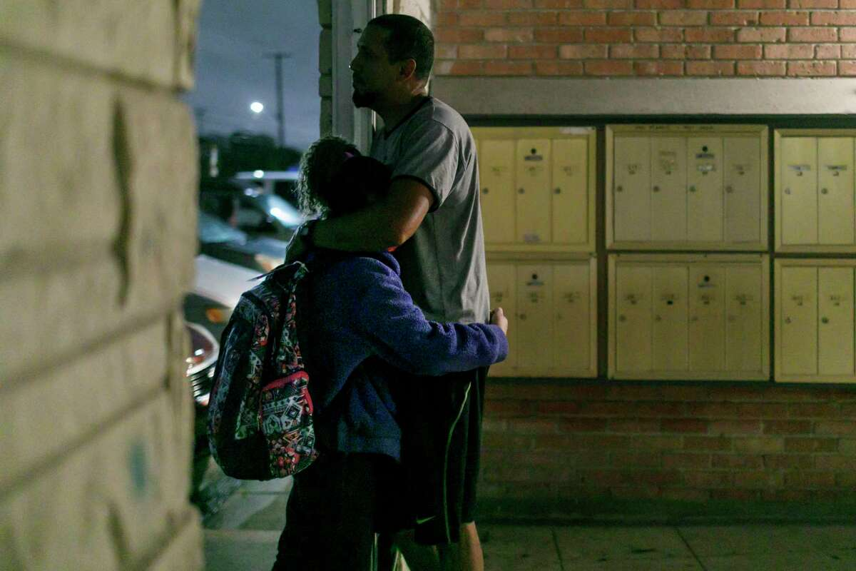Larry Gomez and his 9-year-old daughter, Maria Gabriela Gomez, who attends Ridgeview Elementary School, wait for her bus in their apartment complex breezeway to avoid rain Wednesday morning.