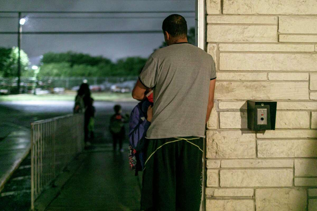 Larry Gomez and his 9-year-old daughter, Maria Gabriela Gomez, who attends Ridgeview Elementary School, embrace as they wait for her school bus before dawn Wednesday. Most area school districts are struggling with shortages of bus drivers and other staff.