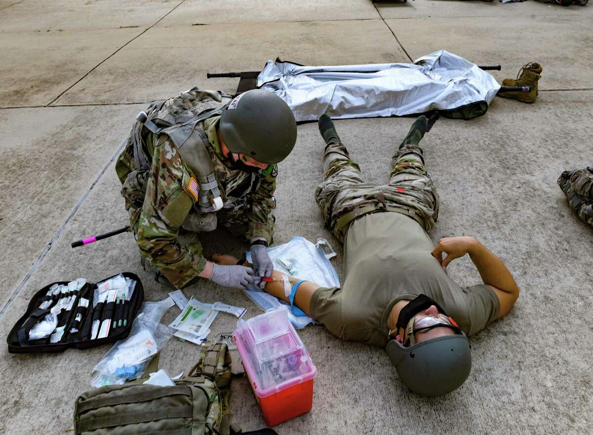 A soldier training to be a combat medic inserts an IV needle in another trainee during an exercise at Joint Base San Antonio-Fort Sam Houston on Aug. 17, 2021.