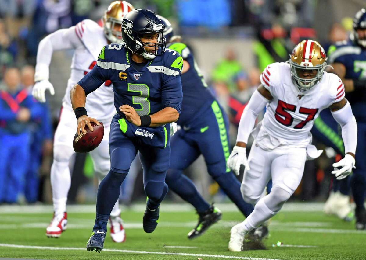 SEATTLE, WASHINGTON - DECEMBER 29: Feeling pressure, Russell Wilson #3 of the Seattle Seahawks rolls out of the pocket during the first quarter of the game against the San Francisco 49ers at CenturyLink Field on December 29, 2019 in Seattle, Washington. (Photo by Alika Jenner/Getty Images)