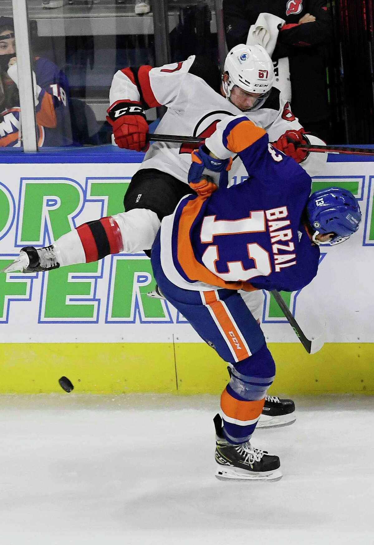 The New Jersey Devils' Marian Studenic is checked by the New York Islanders' Mathew Barzal during a preseason game Saturday in Bridgeport.