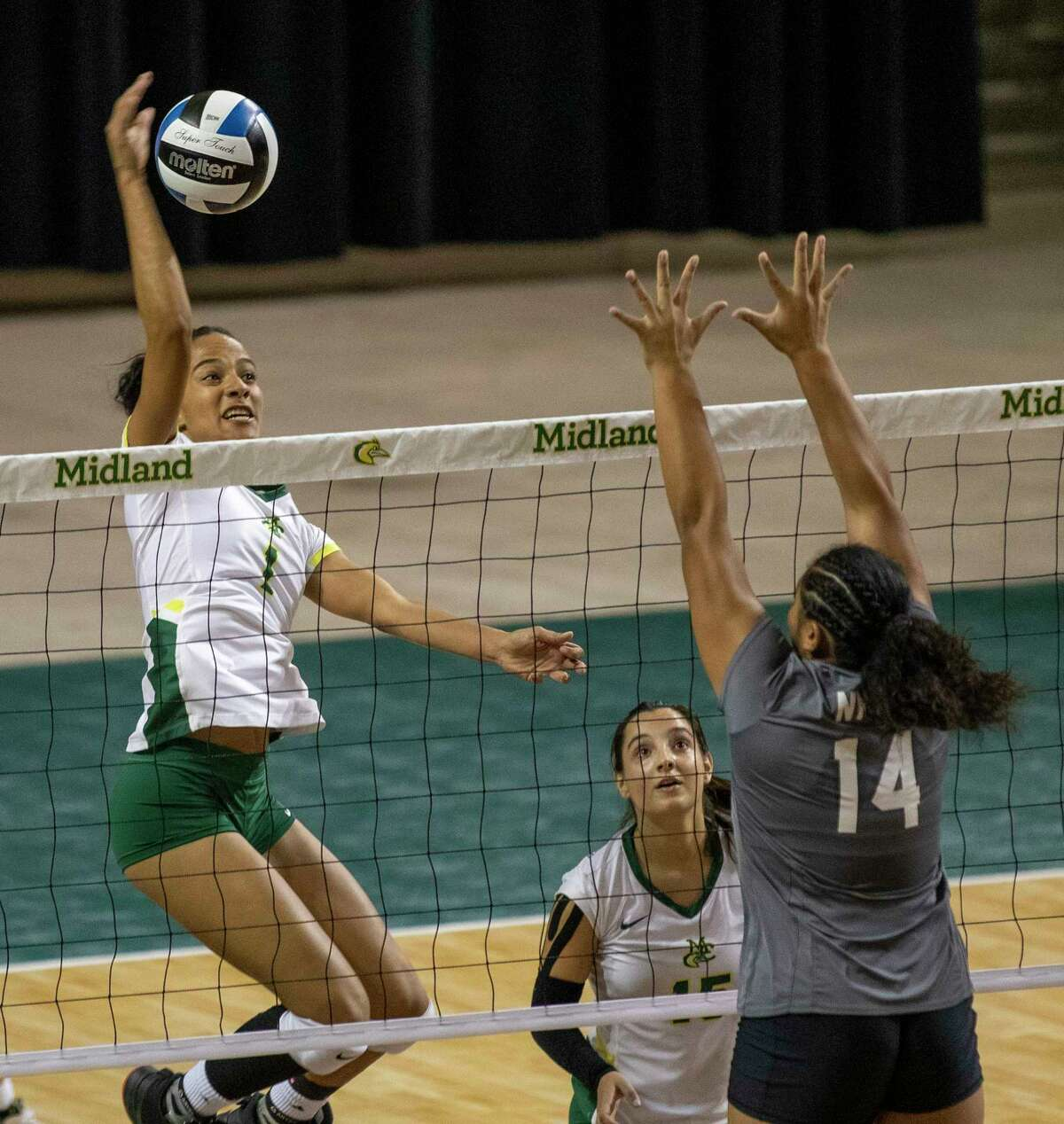 Midland College's Lindamara Conceicao (1) hits the ball past New Mexico Military Institute's Allyah Tokelau (14) on Saturday, Oct. 2, 2021 at Chaparral Center. Jacy Lewis/Reporter-Telegram