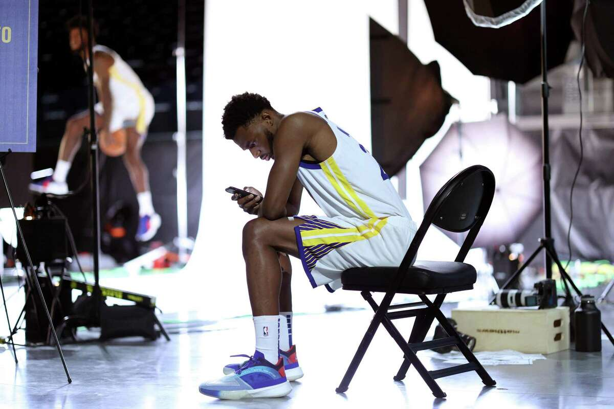 SAN FRANCISCO, CALIFORNIA - SEPTEMBER 27: Andrew Wiggins #22 of the Golden State Warriors checks his phone during the Golden State Warriors Media Day at Chase Center on September 27, 2021 in San Francisco, California. (Photo by Ezra Shaw/Getty Images)