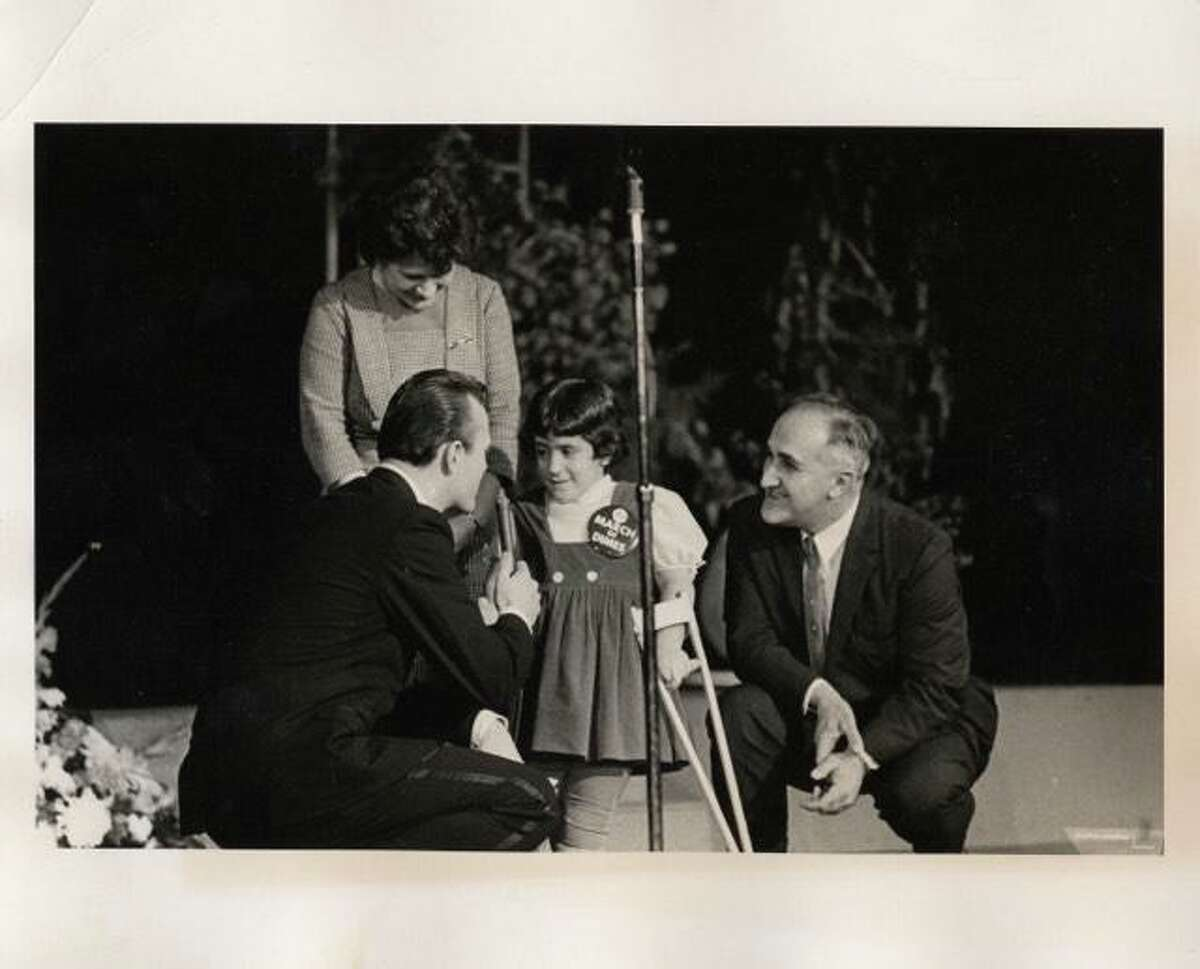 Primetta (left) and Umbert Giacopini (right) standing with their daughter, Dorene Giacopini (center) as she is interviewed.