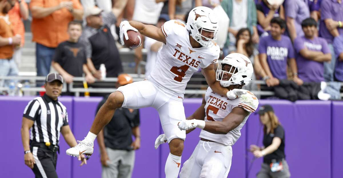 Texas wide receiver Jordan Whittington (4) and teammate running back Bijan Robinson (5) celebrate Whittington's touchdown pass against TCU during the second half of an NCAA college football game Saturday, Oct. 2, 2021, in Fort Worth, Texas. Texas won 32-27. (AP Photo/Ron Jenkins)