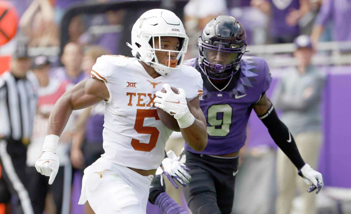 Texas running back Bijan Robinson (5) runs for a touchdown as TCU cornerback C.J. Ceasar II (9) pursues during the first half of an NCAA college football game Saturday, Oct. 2, 2021, in Fort Worth, Texas. (AP Photo/Ron Jenkins)