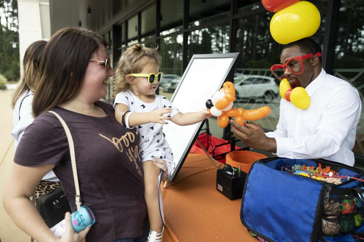 Louie Balloonie, right, hands Eloise Gleason, 2, a balloon animal tiger during the Creekside Park West Fall Festival, Saturday, Oct. 2, 2021, in The Woodlands. Featured activities included face painting, balloon animals and a pumpkin patch.