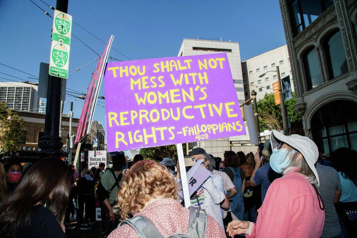 """A San Francisco protester carries a sign saying """"Thou shall not mess with women's reproductive rights. Fallopians 4:28."""""""
