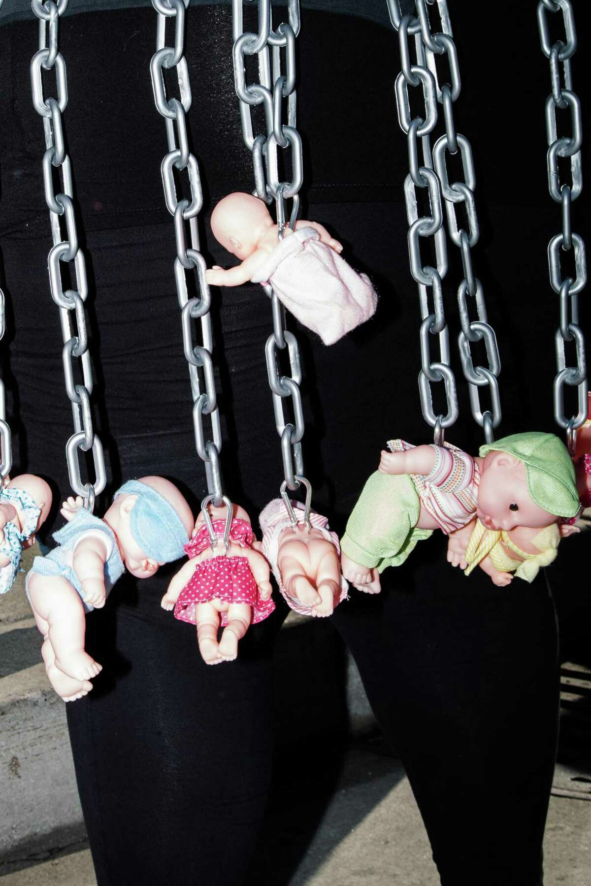A protester carries chains with baby dolls attached at the march in support of reproductive rights in San Francisco.