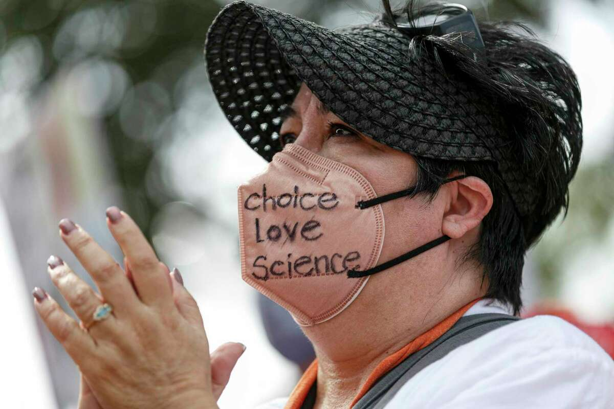 """Sandra Fuentes listens to speakers as she wears a mask that says """"pro choice, pro love, pro science"""" at the rally."""