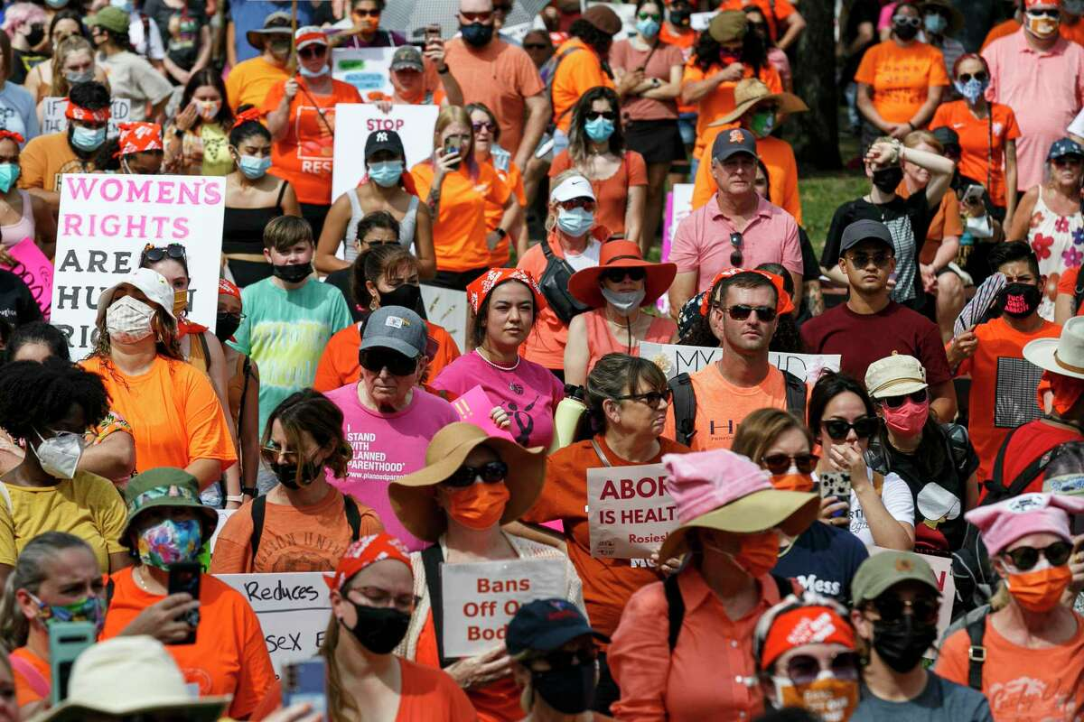 """A large crowd listens to speakers during the """"Bans Off Our Bodies"""" abortion-rights rally held Saturday, Oct. 2, 2021, at Milam Park. Many of the participants were wearing orange, harking back to 2013 when former state Sen. Wendy Davis wore orange during a 13-hour filibuster to block abortion restrictions."""