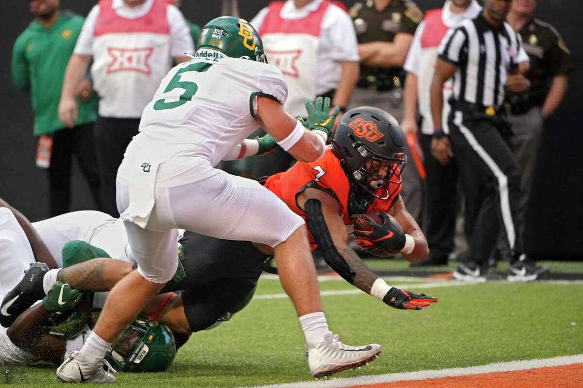 Oklahoma State running back Jaylen Warren (7) dives into the end zone in front of Baylor's Dillon Doyle (5) for a touchdown in the first half of an NCAA college football game, Saturday, Oct. 2, 2021, in Stillwater, Okla.