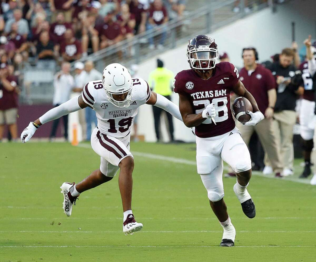 COLLEGE STATION, TEXAS - OCTOBER 02: Isaiah Spiller #28 of the Texas A&M Aggies is pursued by Collin Duncan #19 of the Mississippi State Bulldogs as he rushes for forty one yards in the first quarter at Kyle Field on October 02, 2021 in College Station, Texas. (Photo by Bob Levey/Getty Images)