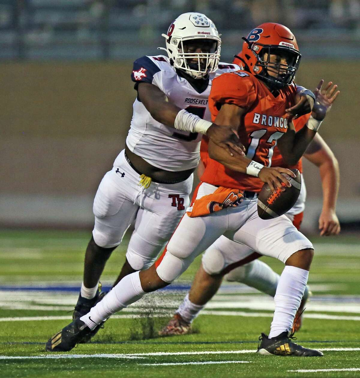 Brandeis quarterback Nico Garcia (13) escapes a tackle of Roosevelt defensive end Bello Olalekan (9) during the UIL football game against Roosevelt on Saturday at Dub Farris Athletic Complex.