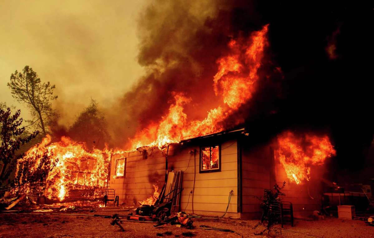 This file photograph shows flames consuming a house near Old Oregon Trail as the Fawn Fire burns about 10 miles north of Redding on Thursday, Sept. 23, 2021.