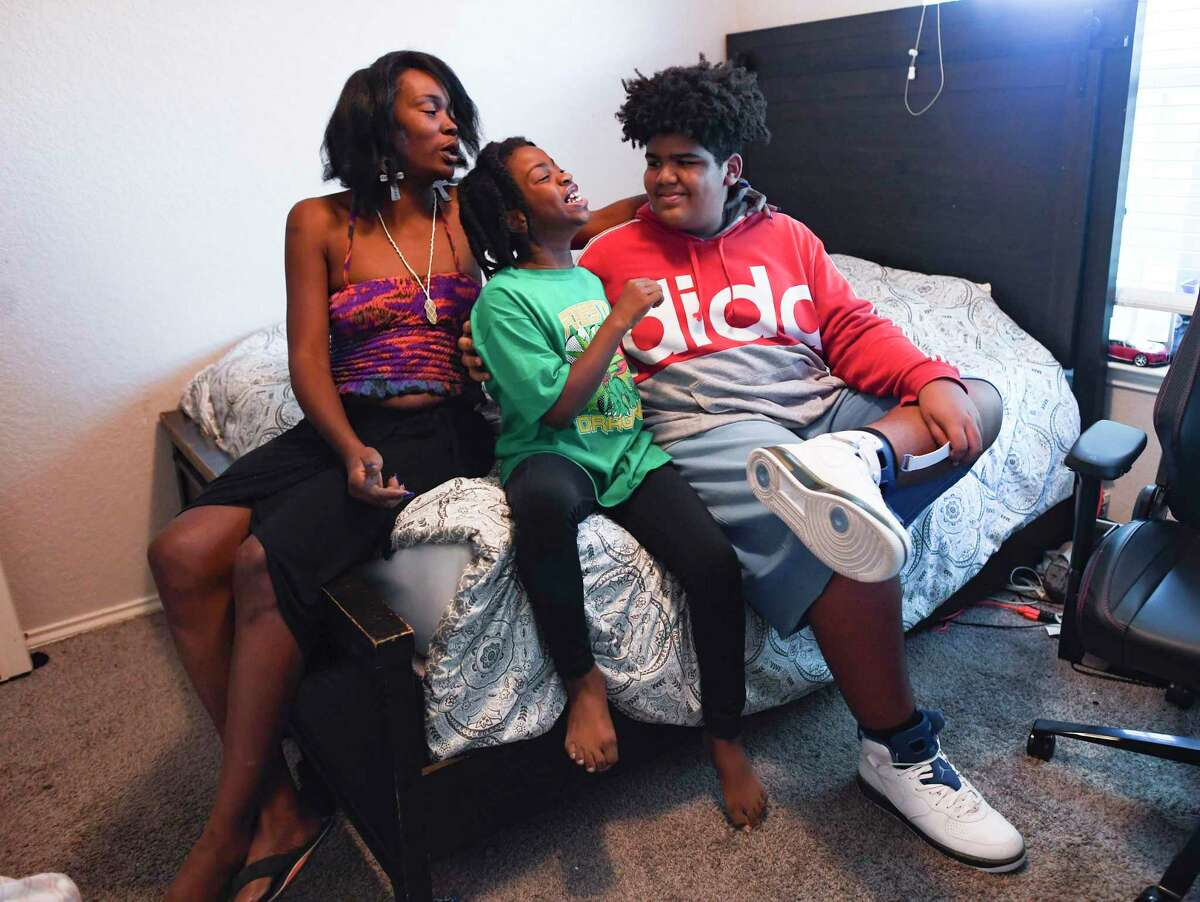 Tiffany Jones, sits with her daughter, McKeilah, and son, Joseph, who is 6 feet, 6 inches tall and wears size 18 shoes. Jones had difficulty finding shoes for Joseph. She put out a call for help on social media, and within days, many responded with shoes, including NBA players.