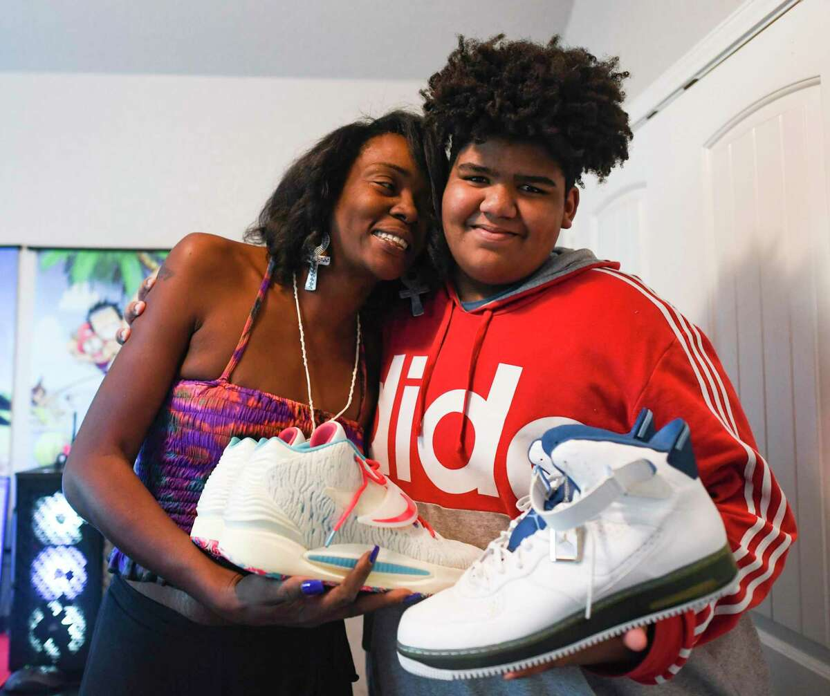 Tiffany Jones embraces her son, Joseph, who is 6 feet, 6 inches tall and wears size 18 shoes. Jones had difficulty finding shoes for Joseph. She put out a call for help on social media, and within days, many responded with shoes, including NBA players.
