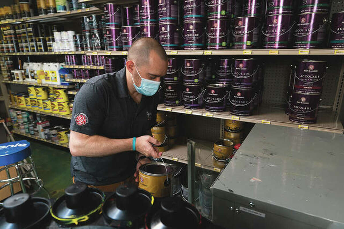 Billy Wommack carries a gallon of paint to a shaker at a mixing station. Chemical shortages, and a near doubling of oil prices in the past year, mean higher prices for many goods. Some hardware stores are only getting 20% to 30% of the paint needed to meet customer demand without backordering; in normal times the so-called fill rate usually runs 90%.