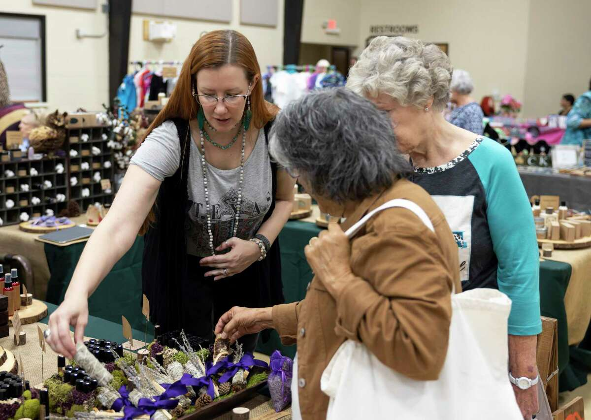 Jaimi Edgmon, center, describes her handmade natural products from Cranky Owl during the Deck the Halls Fall and Christmas Market at First Baptist Church, Friday, Oct. 1, 2021, in downtown Conroe. The event lasted for two days featuring many local homecraft makers.