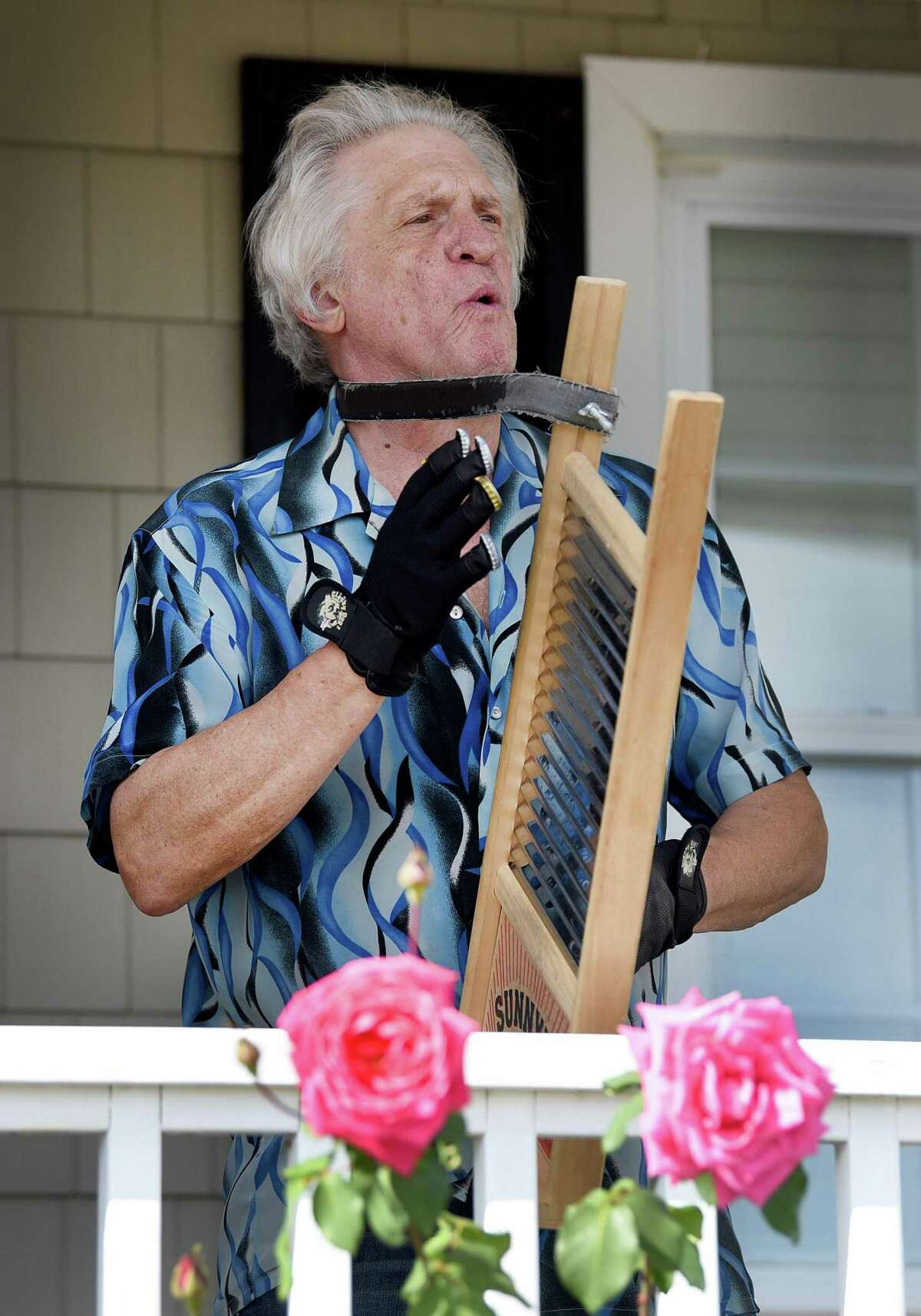 """Peter Menta, of Hamden, plays the washboard with the """"Sweet Louise Band"""" during Milford Porch Fest Saturday."""